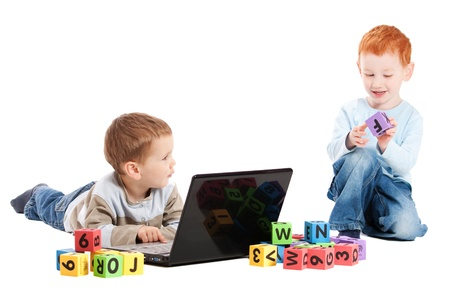 Boys with computer and blocks. Isolated on whaite photo