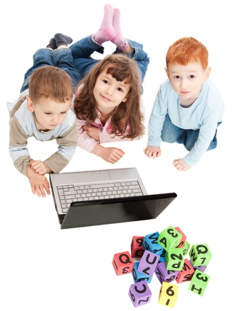 Children learning with computer and alphabet blocks. Isolated on white photo