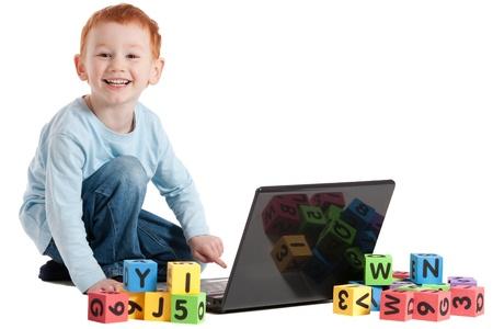 en cuclillas: Niño leyendo el aprendizaje con ordenador portátil y los bloques de los niños. Aislado en blanco. Foto de archivo