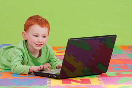 Boy using notebook computer on alphabet letters mat. photo