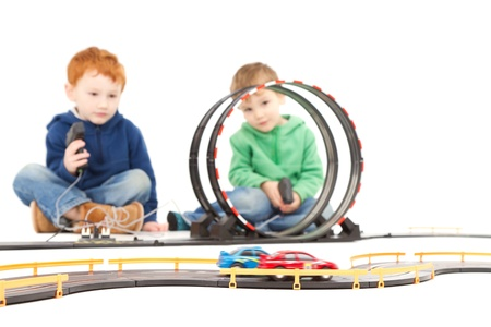 electric automobile: Children playing kids racing toy electric slot car game  On white