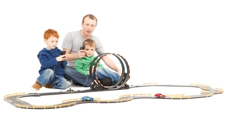 electric automobile: Father and children playing kids racing toy electric slot car game  On white  Stock Photo