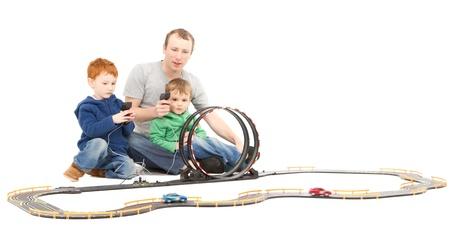 Père et enfants qui jouent les enfants de course jouet jeu voiture électrique fente sur blanc