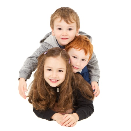 sibling: Three happy children laying down in pile  Isolated on white