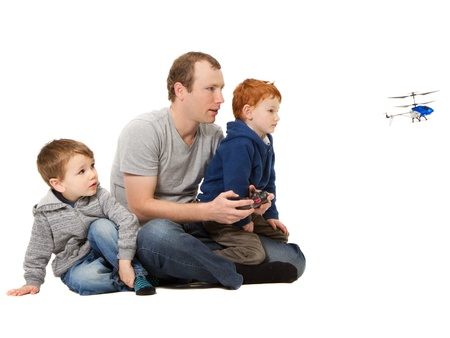 babysitting: Father and sons playing kids radio controlled helicopter game  On white