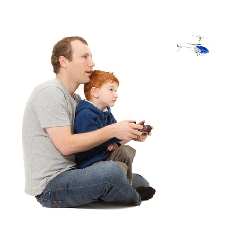 Father and son spending time playing together flying radio controlled helicopter  Stock Photo