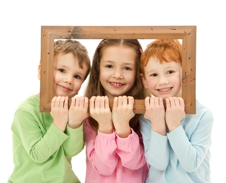 Three happy smiling kids looking through picture frame  Isolated on white