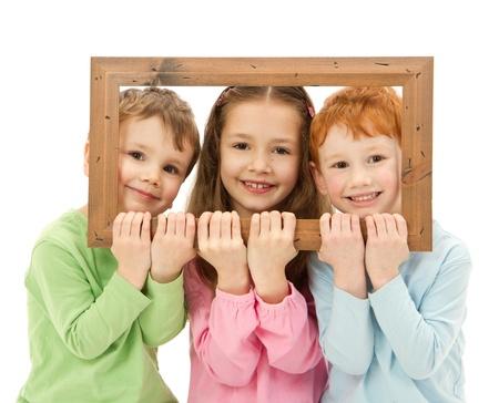 Trois gosses heureux souriant en regardant à travers cadre photo isolé sur blanc