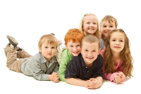lay down: Group of six children laying down on other kdis on floor together  Isolated on white  Stock Photo