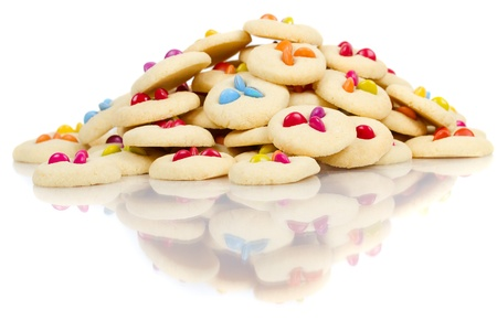 Pile of cookies with smarties on white with reflections photo
