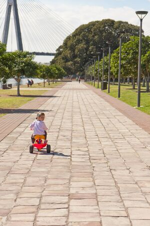 tricycle: Young girl riding trike in city park with harbour and bridge background Stock Photo