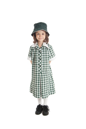five year: Young girl in school uniform and sun hat  Isolated on white