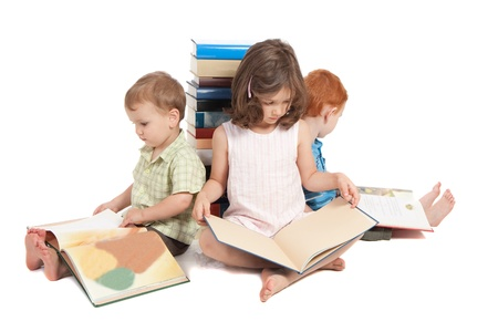 literacy: Three kids sitting on floor reading books and leaning against stack  Isolated on white