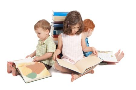 Trois enfants assis sur les livres de lecture de sol et adossé à pile Isolé sur fond blanc