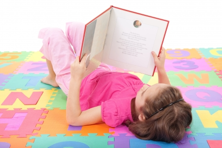 preparatory: Girl reading book on alphabet letters floor mat  Isolated on white