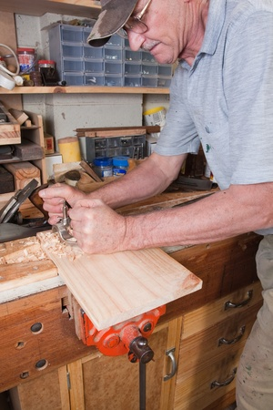 Man using routing plane on workbench with tools and odds and ends in background Stock Photo - 15155187