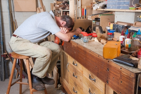 clutter: Older man with head on arms in his workshop surrounded by tools and equipment Stock Photo
