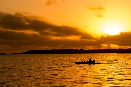 Silhouette de pêcheur en kayak et orange coucher de soleil lac