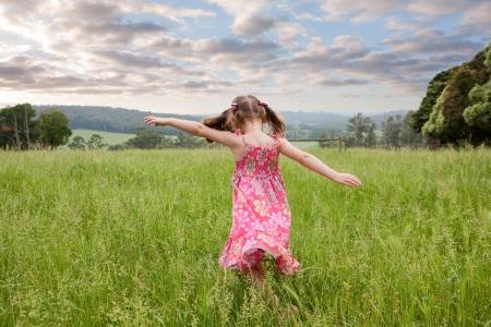Fille qui traverse le terrain herbe longue avec les bras tendus