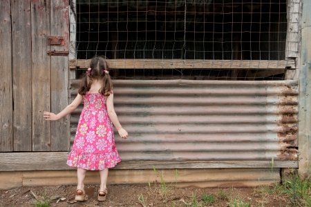 tiptoes: Young inquisitive girl peering into old shed on tiptoes