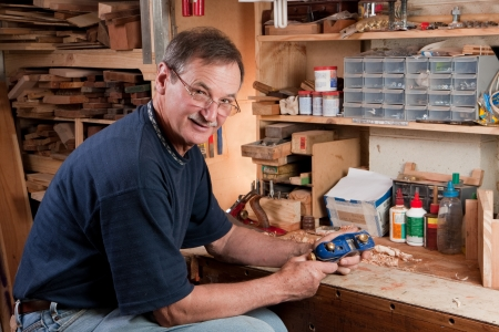 Senior man sitting at workbench in workshop with plane