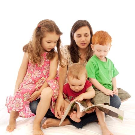 Lecture maman de trois jeunes enfants sur les genoux Banque d'images