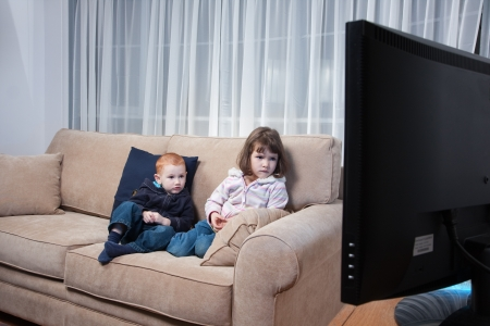Two kids sitting on couch watching television