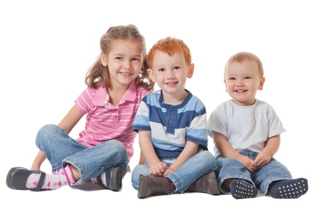 Three kids smiling and sitting on the ground Stock Photo