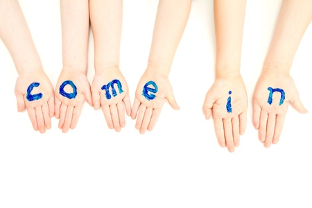 kids painted hands: Kids hands with come in welcome painted on them  On white