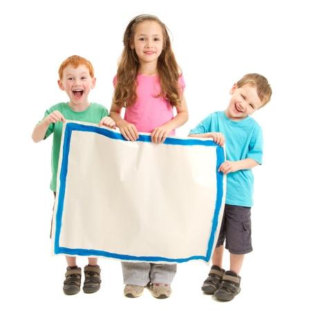 Trois enfants heureux holding signe blanc peint Isolé sur fond blanc Banque d'images
