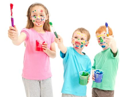 messy kids: Messy kids holding paint brushes  Isolated on white