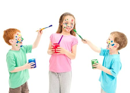 Children painting faces on each other with paint  Isolated on white  photo