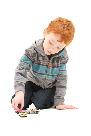 Boy child playing with toy cars  On white