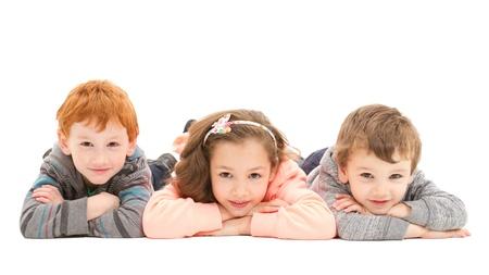 Three kids laying on floor.  Isolated on white. Standard-Bild