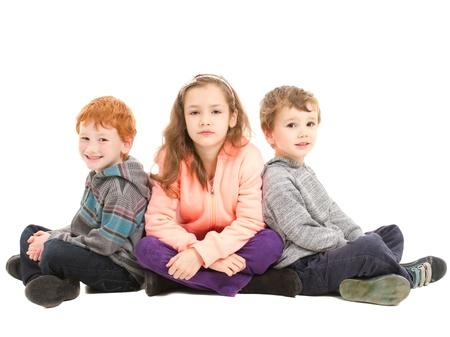 trois enfants: Trois enfants assis les jambes crois�es sur le sol en attendant patiemment. Sur fond blanc.