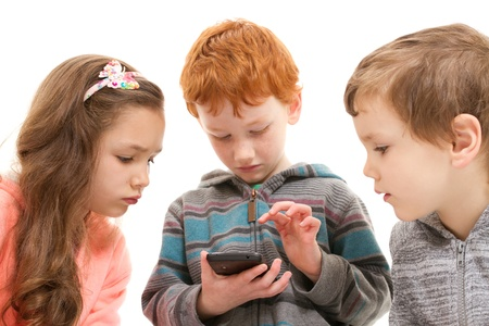 Three children watching child using smartphone. Isolated on white. photo