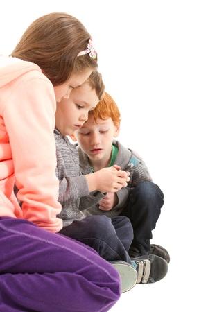 Three children sending sms on mobile phone. On white. Stock Photo - 20174600