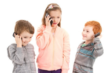 Three children talking on mobile phone. Isolated on white. photo
