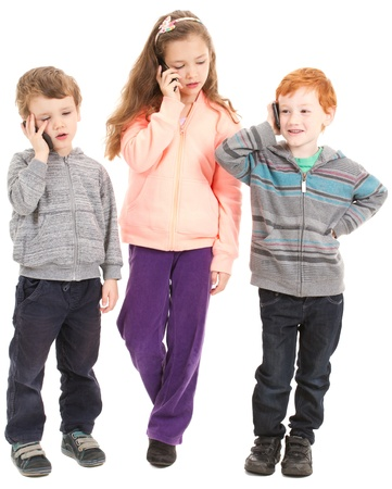 Group of three children talking on kids mobile phones. Isolated on white. photo