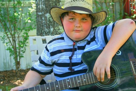 Young boy playing guitar outside