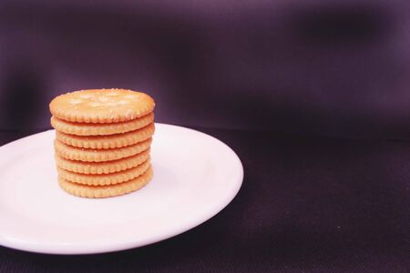 buttery: Stack of yellow crackers on plate Stock Photo