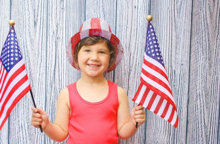 Girl waving flags on 4th of july photo