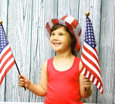 Young girl with 4th of july hat and flags photo