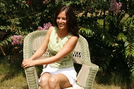 Portrait of a pretty young woman sitting in wicker chair photo