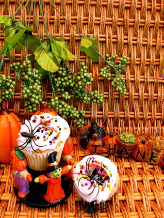 Two halloween decorated cupcakes with green leaves in background photo