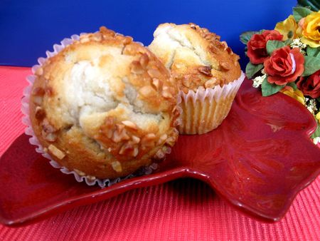 Two homemade banana nut muffins on plate with flowers in background 스톡 콘텐츠