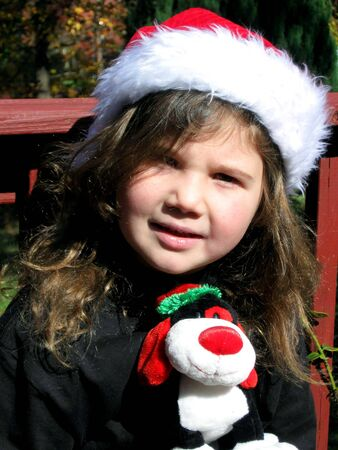 Pretty little girl wearing santa hat sitting outside photo