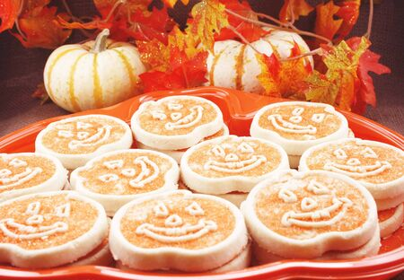 Halloween cookies with pumpkins and fall leaves in background photo