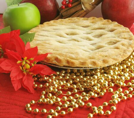 Apple pie on shelf with christmas decorations in background photo