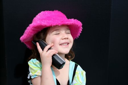 Happy little girl in pink hat talking on telephone photo